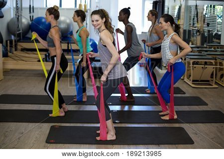 Fit women performing stretching exercise with resistance band in gym