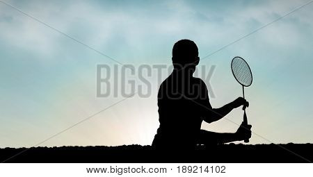 Digital composite of Silhouette man playing badminton against sky