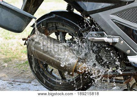 Washing scooter outdoors. Throwing water. Horizontal image.