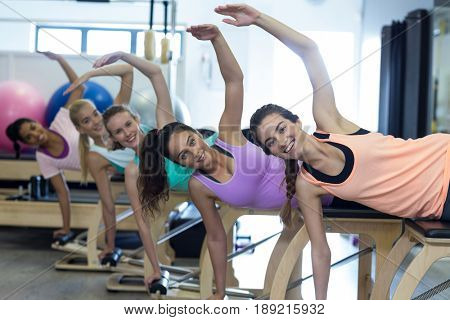 Group of smiling women exercising on wunda chair in gym