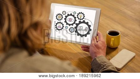 Digital composite of High angle view of woman looking at gears in digital tablet
