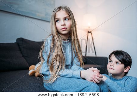 Cute Little Boy Kneeling And Looking At Pensive Little Sister Sitting On Bed