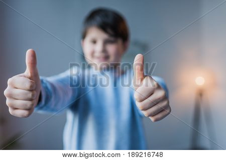 Close-up View Of Little Boy Showing Thumbs Up And Smiling