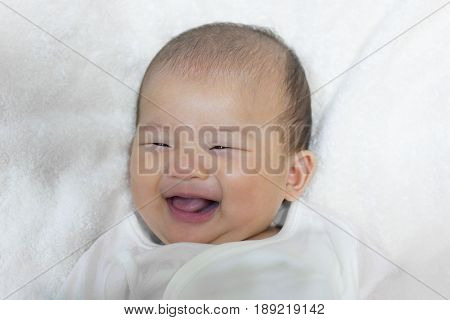 Close - Up Two month old new born asian cute baby smile rests happily on white bed background.