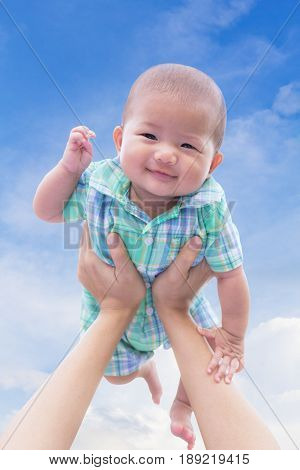 Close - Up Asian cute new born baby smile happily with holding hands mother on blue sky background.
