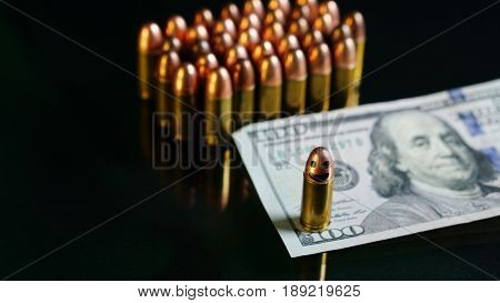 9mm bullet and US 100 dollars on the black mirror background.