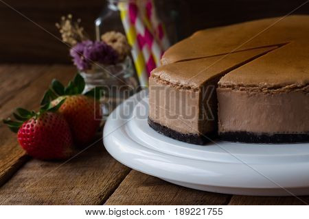 Homemade chocolate cheesecake on rustic wood table.Baked chocolate cheesecake on plate.Brownie cheesecake for coffee break or tea time in cafe.Triangle slice piece of chocolate cake in natural style. Dark chocolate brownie cheesecake.