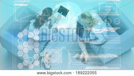Digital composite of Digitally generated image of various icons with business people discussing in office