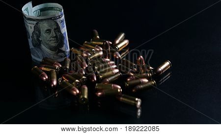 9mm bullets and US 100 dollars on the black mirror background.
