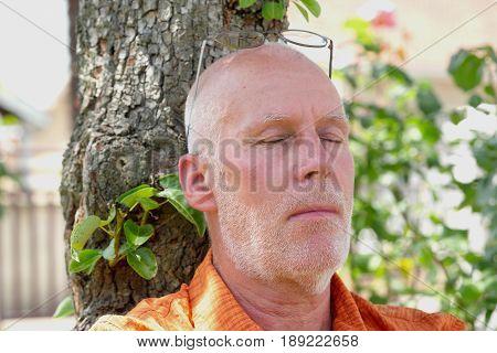 A senior takes a nap under a tree