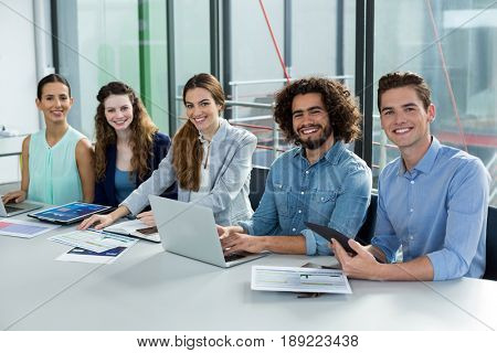 Smiling business team working on laptop and digital tablet in meeting at office