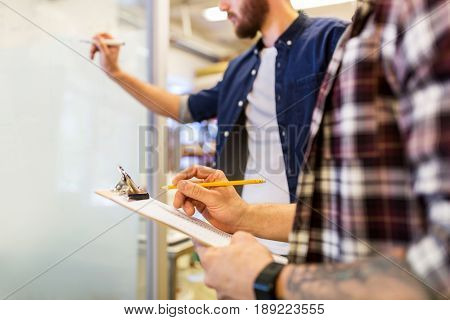 business, manufacture and people concept - men writing to clipboard and whiteboard at office