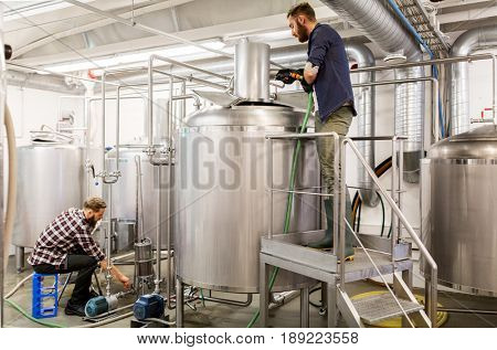 alcohol production, business and people concept - men working at craft beer brewery kettles