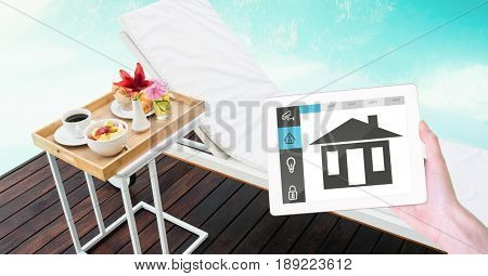 Digital composite of Hand holding digital tablet with smart home application on screen at poolside