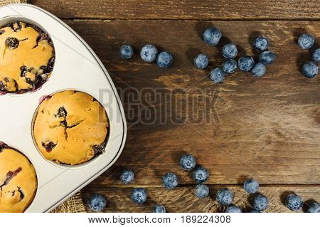 An overhead photo of freshly baked homemade muffins in a pan, with fresh blueberries on a dark rustic texture and a place for text