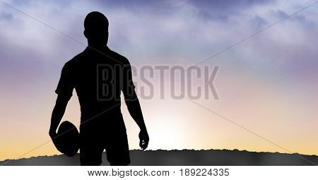 Digital composite of Silhouette sportsman holding rugby ball during sunset
