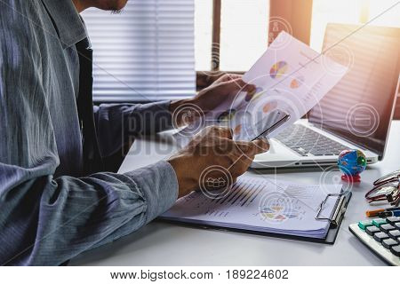 Businessman working with smart phone and discussing the analysis charts or graphs on modern White office desk table .Business concept.