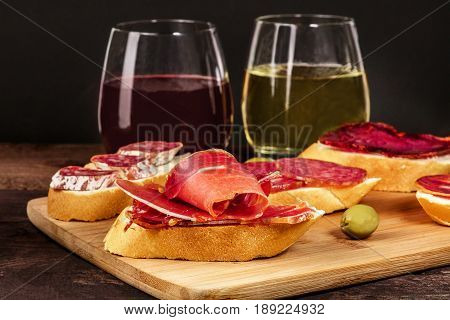 A photo of embutidos tapas, sandwiches with jamon, salchichon, lomo, and other Spanish sausages, with glasses of wine and green olives, on a dark background with a place for text