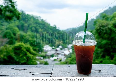 Ice back Coffee on wooden table and blurred green forrest with house background.Close up