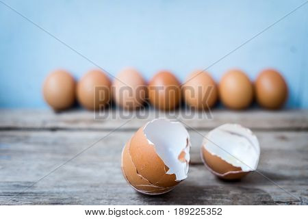 Close-up of two egg shell and fresh eggs on wooden background.