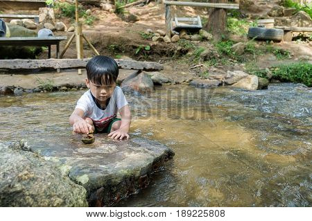 Asian boy swimming in an oasis pool with waterfal and stacked stones.Close up