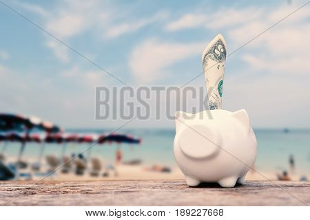 Piggy bank and money on table and sea background concept save money to travel