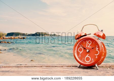 alarm clock on table and sea background concept time to travel