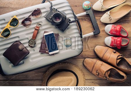 Clothing traveler's Passport wallet glasses smart phone devices on a wooden floor in the luggage ready to travel with family