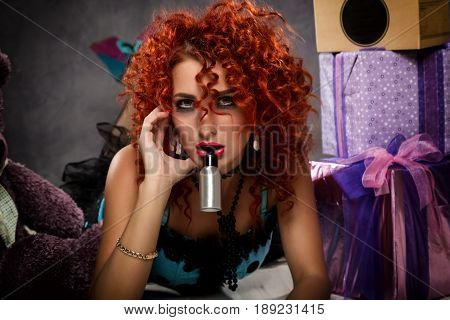 Curly redhead sexy girl looks like a doll for adult men. popsy sucks from a small bottle. Beside sits teddy bear and gift boxes