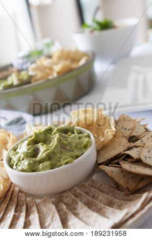 Mexican tacos nachos tortillas and guacamole. In a dish is potato salad with cherry tomatoes and parsley to garnish, and the other a typical Mexican dish of guacamole and tacos.