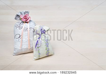 Two lavender scent sachets on wooden board or table. Scented pouches on wood with copy space. Fragrant bags for fresh home. Decoration, furnishing and storage items. Aromatic potpourri set.