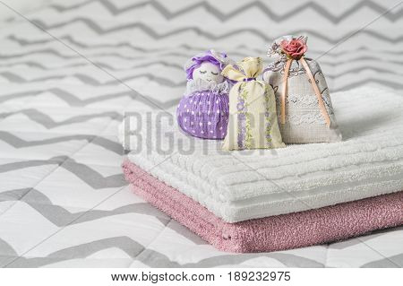 Scented sachets and fragrant pouch figure of a girl. Bags filled with lavender in bedroom. Towels on bed. Fragrance bags for fresh home. Decoration, furnishing and storage items.