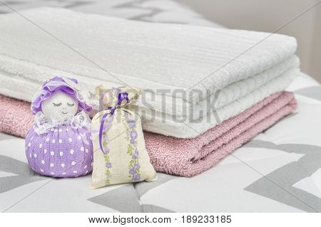 Scented pouch and lavender sachet figure and character representing a girl or woman. Dried lavender in decoration bags in bedroom and towels on bed. Aroma potpourri and furnishing items.