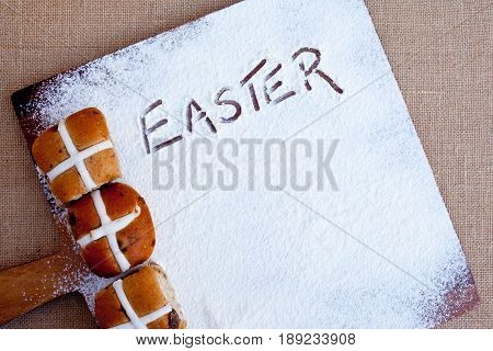 Easter - Hot Cross Buns on floured wooden cutting board, with word Easter written in flour