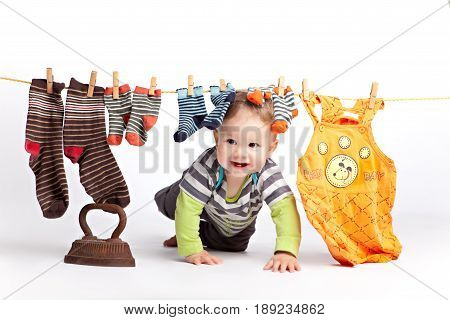 Baby crawls on all fours under the clothesline, on which hang clothes washed and socks. On the floor is an old rusty vintage iron