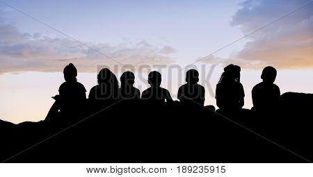 Digital composite of Silhouette kids sitting on hill against sky