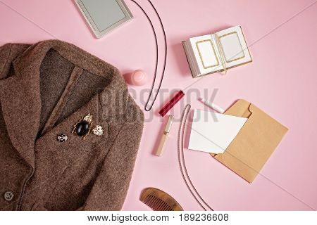 Flat lay feminine background: woman clothes and accessories: coat brooches clean paper in envelope comb necklace lipstick ebook and other on pale pink background. Top view beauty blog concept.