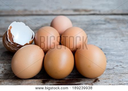 fresh eggs and egg shell on wooden background.