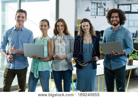 Portrait of smiling business executives standing with digital tablet, mobile phone and laptop in office