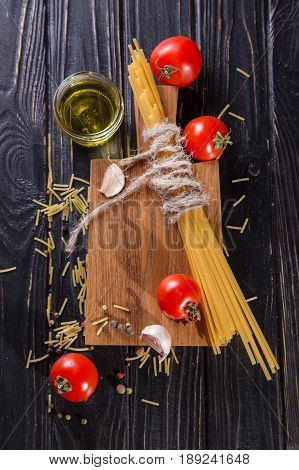 raw spaghetti with tomatoes and oil on black in studio