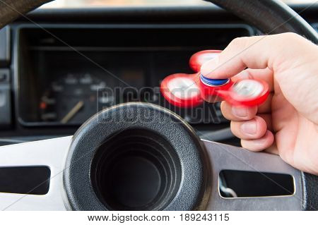 Close-up of a man's hand playing with a spinner while in a traffic jam on the background of the steering wheel of a car popular fidget spinner toy.