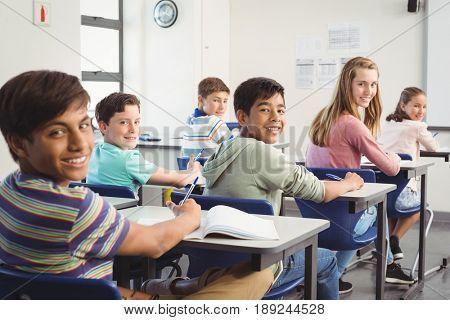 Portrait of smiling school kids doing homework in classroom at school