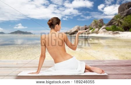 beauty, people and bodycare concept - beautiful young woman in white towel with bare top holding something invisible over exotic beach background