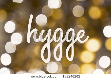 holidays and cosiness concept - word hygge over blurred golden lights background