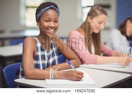Portrait of student sitting at desk in classroom