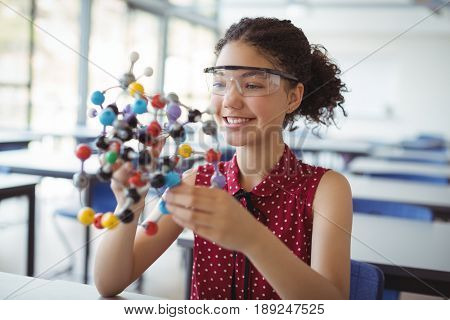 Happy schoolgirl holding experimenting model in laboratory at school