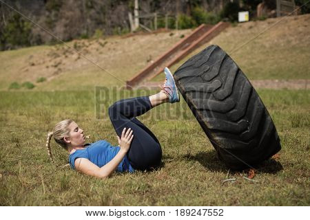 Fit woman performing leg workout with tier during obstacle course in boot camp