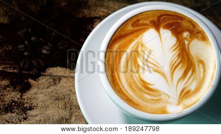 Hot cappuccino or latte art coffee. A cup of coffee on the wooden table with dark roasted coffee beans. Morning breakfast with coffee. Latte art created by pouring steamed milk.
