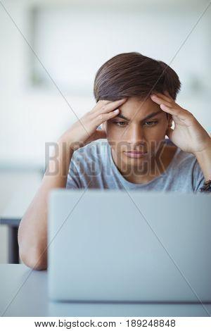 Tensed schoolboy looking at laptop in classroom at school