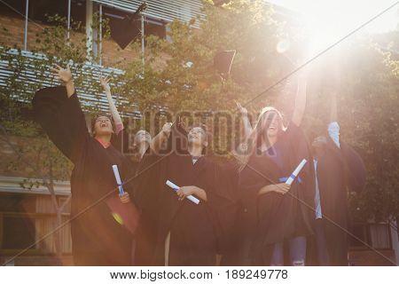 Successful graduate school kids throwing mortarboard in air in campus at school